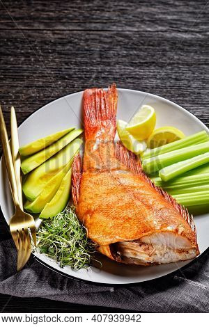 Cold-smoked Red Snapper Served With Celery Sticks, Avocado Slices And Microgreens On A Grey Plate On
