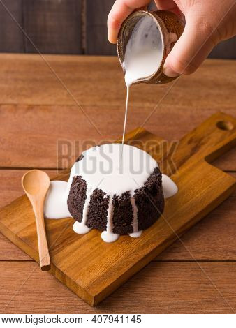 Pouring Milk Sauce Onto Chocolate Brownies On Wooden Plate And Wooden Background. Homemade Bakery An