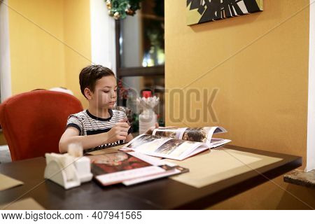 Boy Examines Magazine In Cafe