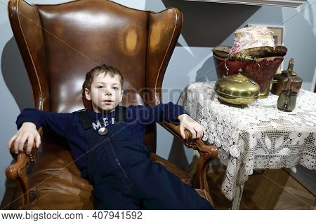 Boy Sitting In Vintage English Leather Chair