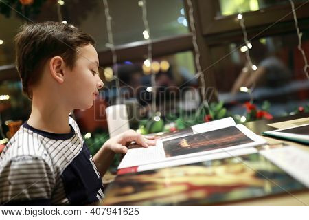 Child Examines Magazine In Cafe