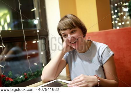 Portrait Of Happy Woman With Magazine In Cafe