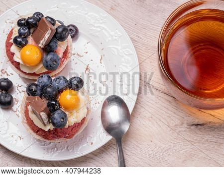Mouthwatering Muffins With Berries And Chocolate And Tea In A Glass Round Cup On A Wooden Background