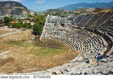 Tourist taking photo on ruins of Theatre in Letoon Ancient City in village Kumluova, Turkey. Sunny day, Greek culture ruins