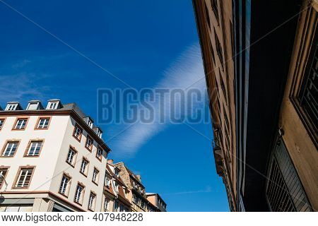 Low Angle View Of French Alsatian Timbered House And Haussmannian Architecture With Clear Blue Sky I