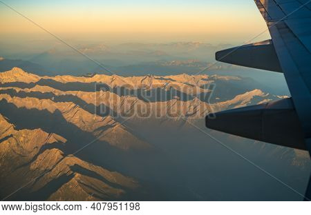 Mountain Range Seen From Airplane, With Plane Wing Seen On The Right Side. Mountains During Sundown,