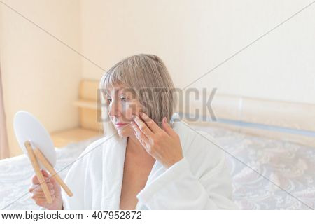 Senior Woman In The Bedroom Applying Anti-aging Lotion. Looks In A Cosmetic Mirror. Concept Anti Age