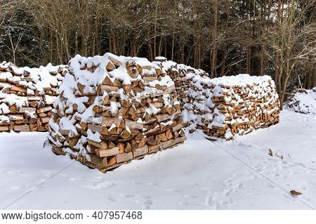 Pile Of Firewood In Winter. Firewood Covered In Snow. Firewood Under The Snow.wood Fuel.