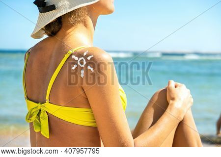 Back View Of Young Woman Tanning At The Beach With Sunscreen Cream In Sun Shape On Her Shoulder. Uv