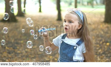 Little Happy Child Girl Blowing Soap Bubbles Outdoors In Summer Park.