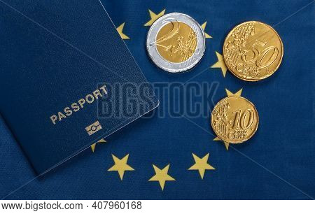 Passport With Coins On The Background Of The Euro Union Flag. Travel Or Emigration Theme