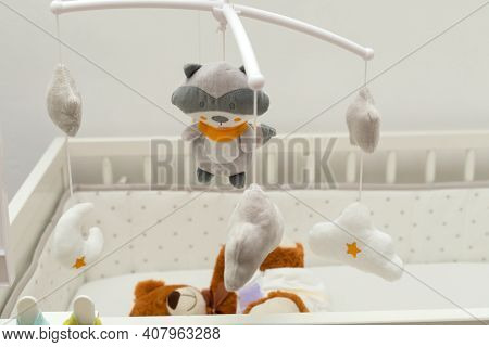 Pcture Of A Brown Teddy Bear With Diaper On Sitting In Baby Bed