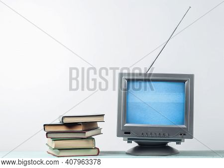 Antenna Old-fashioned Retro Tv Receiver And Stack Of Books On White Wall Background