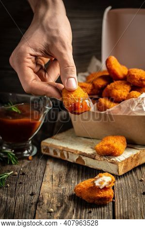 Close-up Of The Hands Holding Home Made Tasty Chicken Nuggets And Sauce In Paper Box On A Wooden Bac