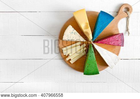 Assortment Of Different Sorts Craft Cheese. Cheeseboard On A White Wooden Background With Copy Space