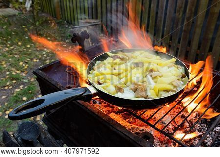 Frying Pan With Fried Potatoes And Mushrooms Over An Open Fire. Cooking Food On A Fire In The Yard.