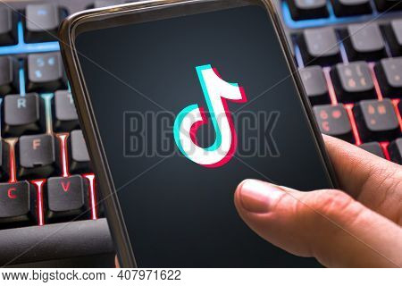 Tiktok Logo With Colorful Background On Smartphone. Social Network For Videos For Young People Close