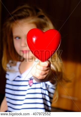 Defocused Little Girl With Red Heart At Home, The Rays Of The Morning Sun Illuminate Dark Room And H