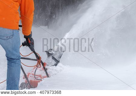 An Adult Man Shot From Back Removing Snow With A Special Blower Device. Snow Removal Equipment With