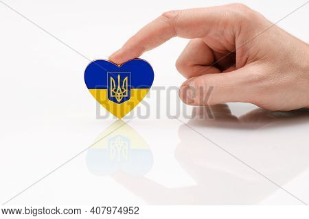 Love Ukraine. Ukraine Flag With Coat Of Arms. A Man's Hand Holds A Heart In The Shape Of The Unoffic