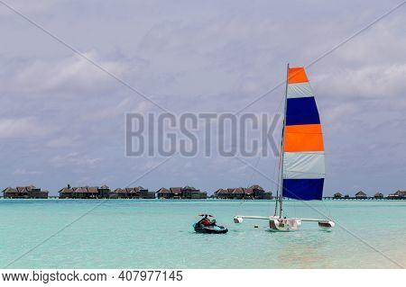 Paradise Island, Maldives - August 28, 2018: A Catamaran Sailing Boat With A Colorful Sail