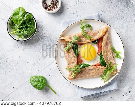 Buckwheat Crepe With Egg, Prosciutto And Spinach On A White Plate. French Cuisine. Gray Background.