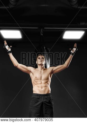 Kickboxing Fighter In Black Gloves And Shorts Posing Against Punching Bag In The Gym. Professional A