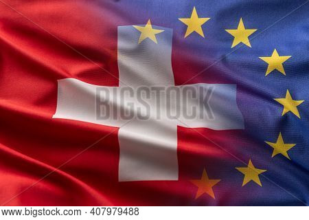 Flags Of Switzerland And Eu Blowing In The Wind.