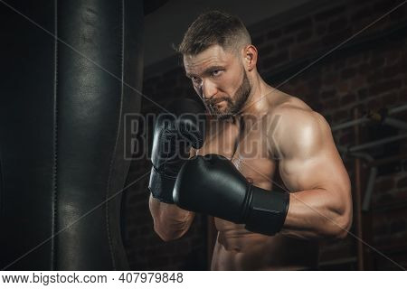 Fighter With Aggression Beats Punching Bag In Black Boxing Gloves In The Gym. Boxer Training Hard, S