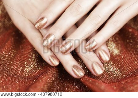Female Hands With Bronze-colored Manicure On A Shiny Bronze Background. Bronze Manicure.