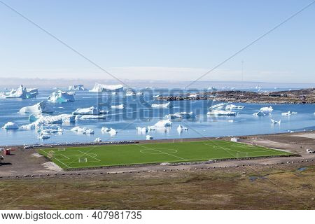 Qeqertarsuaq, Greenland - July 6, 2018: The Local Soccer Field With Icebergs In The Background