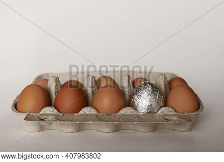 A Dozen Chicken Eggs In A Container. 9 Brown Chicken Eggs, One Silver Egg For Easter. Eggs On A Whit