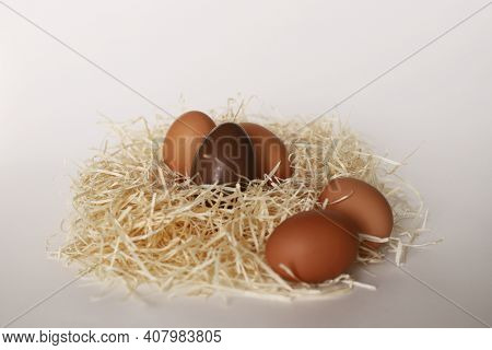 Chicken Eggs On A White Background. Four Chicken Eggs Lie In The Hay. White Background. One Chocolat