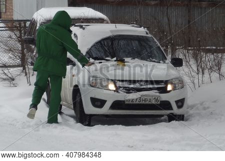 Kazakhstan, Ust-kamenogorsk, February 7, 2020: Man Cleaning Car From Snow In Winter. Green Clothes.