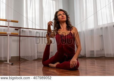 A Young Woman Fitness Instructor In Red Sportswear Leggings And Top Stretching In The Gym Before Her