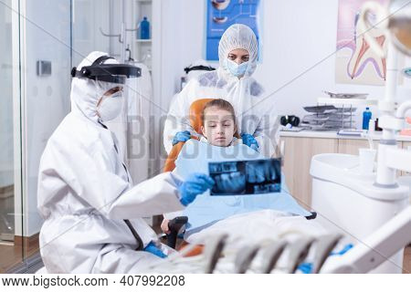 Orthodontist In Ppe Suit Using Dental Radiography To Explain Dentistiry Procedure For Mouth Hygine.