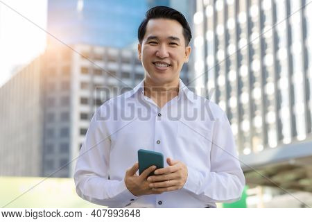Portrait Happy Asian Man Holding Smart Phone And Looking At Camera With Smile Face In Cityscape Back