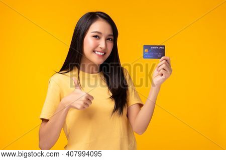 Young Asian Woman Showing Plastic Credit Card Giving Thumb Up To Credit Card, Standing Over Yellow B