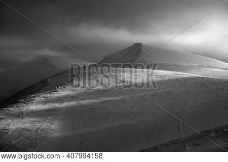 Grayscale. Snow Covered Mountain Slope In Last Evening Sunlight. Magnificent Windy Dusk On Picturesq