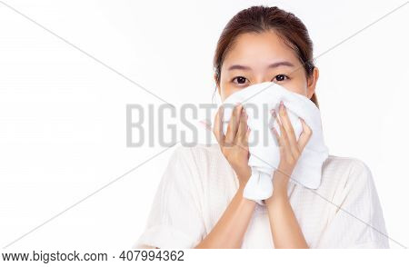 Young Asian Woman Wiping Face With Towel In Bathroom, White Background. Cleaning Face Skin. Portrait