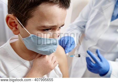 Portrait Of A Scared Male Child In A Medical Mask Receiving A Dose Of Infectious Disease Vaccine