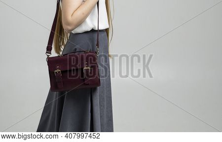 Small Red Leather Bag Over A Woman Shoulder On A White Background. Shoulder Handbag. Woman In A Whit