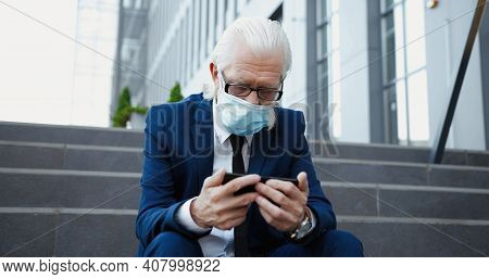 Old Caucasian Businessman Pensioner In Suit, Tie And Medical Mask Sitting On Steps Outside And Watch