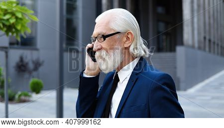 Close Up Of Caucasian Old Good-looking Gray-haired Man In Glasses Talking On Mobile Phone Outdoors.