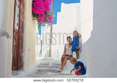 Young Mother And Her Two Daughters Sitting On Doorstep At Old Greek House In The Street Emporio,sant
