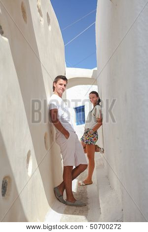 Young Man Front His Beautiful Wife In The Background In A Narrow Street Of The Village Of Emporio