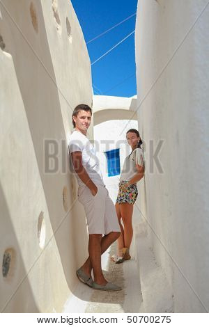 Young Couple In Love Walking On Narrow Streets Of The Village Emporio, Santorini, Greece