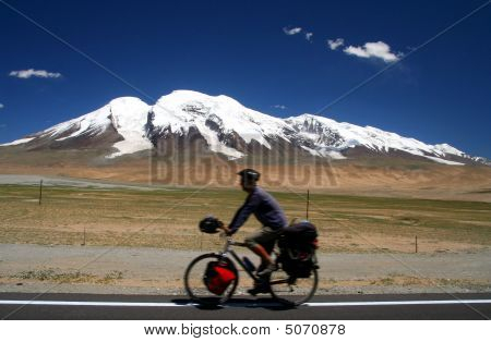 Cycling through remote mountain road in China poster