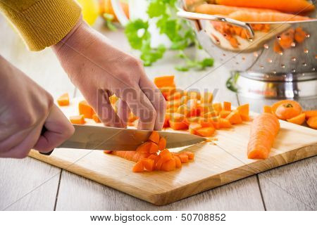 Woman Chopping Carrots With Knife On Board