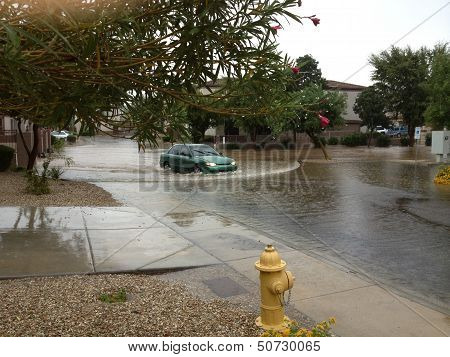 PHOENIX US - SEPTEMBER 9, 2013: Car slowly driving through flooded road after heavy seasonal monsoon